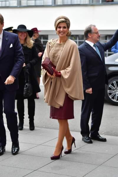 Maxima des Pays-Bas en jupe en cuir rouge bordeaux accessoirisé d'une cape camel à Dessau en Allemagne le 10 février 2017