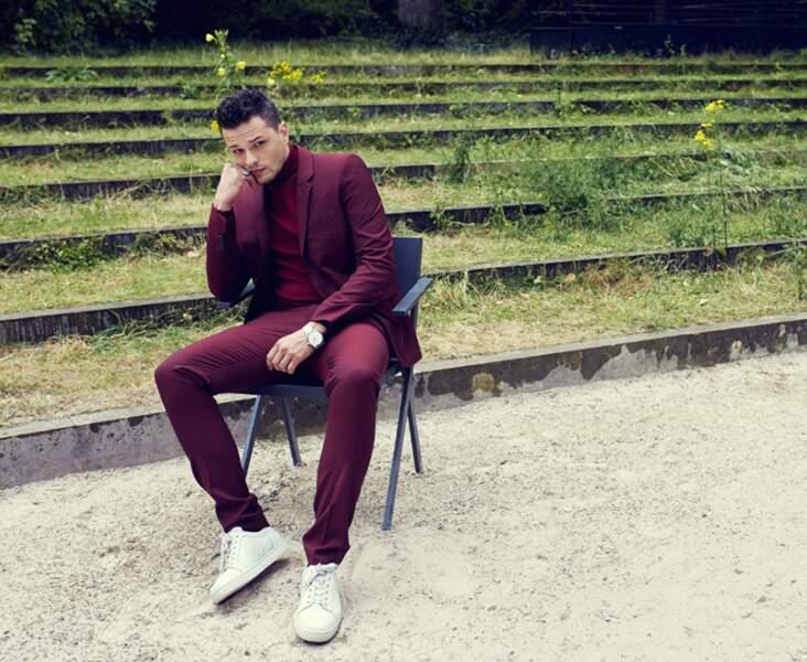 Jules Benchetrit porte un Costume The Kooples, un Col roulé Maison Montagut, une montre Montblanc, sneakers Christian Louboutin.