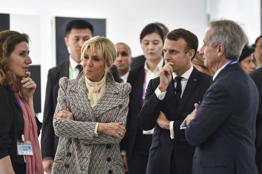 Brigitte Macron à Shanghaï le 5 novembre 2019 très chic avec une blouse crème col lavallière, un petit chignon et un manteau graphique