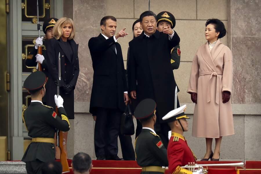 Brigitte Macron a opté pour un manteau noir aux boutons rouges, une robe noire et une paire de gants noirs face à Lady Peng Liyuan, la première dame chinoise