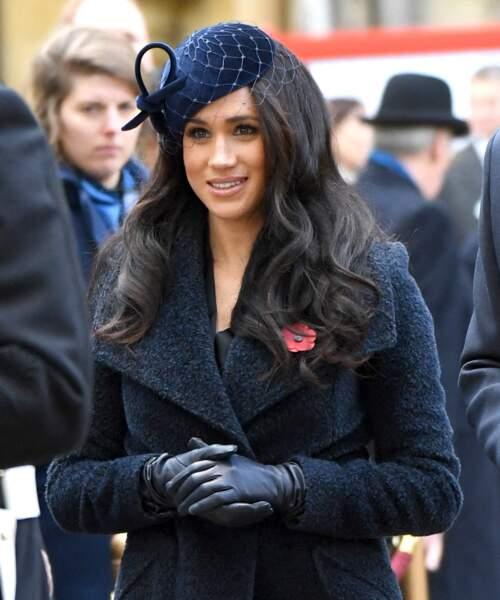 Vêtue d'une long manteau bleu marine Sentaler sur une robe noire, Meghan Markle portait un look très sobre.