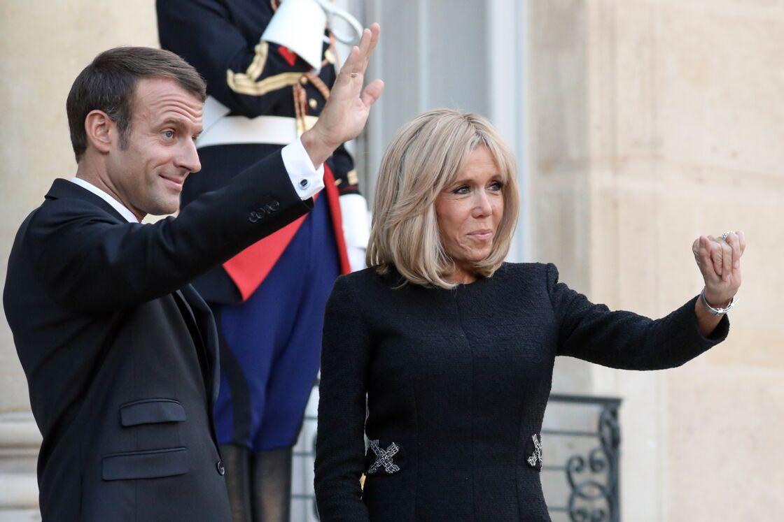 Emmanuel et Brigitte Macron souriants sur le perron de l'Élysée