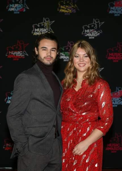 Heloise Martin, tout sourire aux côtés d'Anthony Colette (danseur) pour les NRJ Music Awards 2019. Pour lui c'est facile, un petit col roulé et le sex-appeal opère. L'actrice a opté pour une jolie robe rouge.