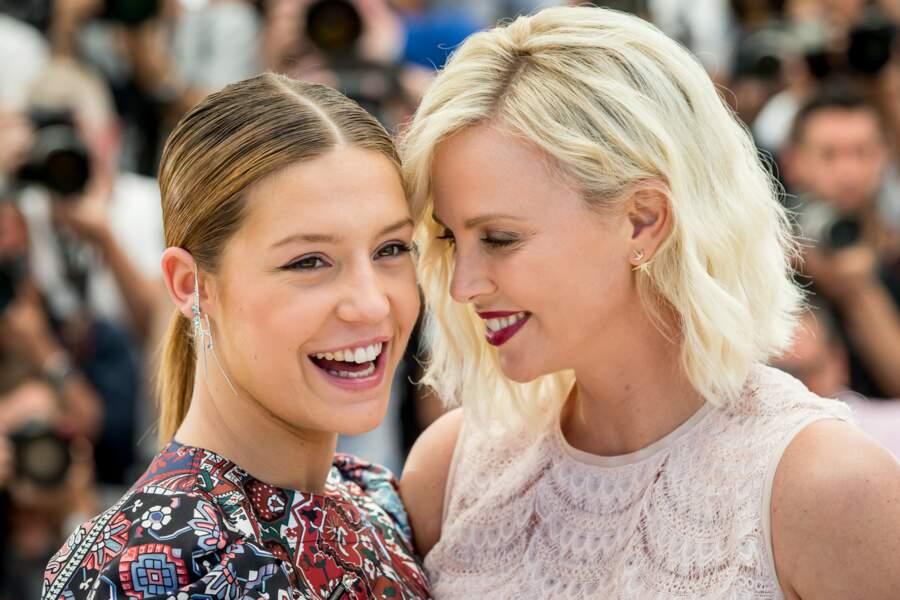 2016 : Charlize Theron est souriante aux côtés de l'actrice Adèle Exarchopoulos lors du 69 ème Festival International du Film à Cannes. Elle porte une coupe décontractée et un blond qui aspire à la décoloration.