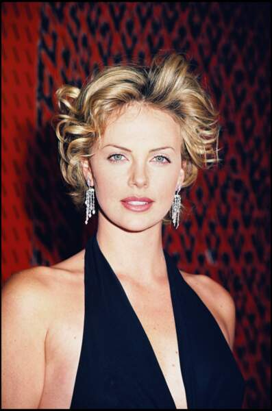2000 : Charlize Theron porte les cheveux courts et bouclés. Sublime, elle participe à la soirée d'anniversaire de Valentino à Hollywood. Un petit côté rétro/bimbo des années 60.