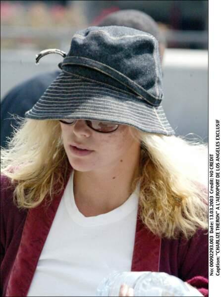 2003 : Charlize Theron à l'aéroport est aussi naturelle que possible. Cheveux en bataille et chapeau de feutre sont de rigueur.