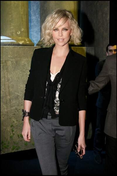2010 : Charlize Theron opte pour les cheveux frisés et une mèche imposante pour se rendre au défilé Dior automne/hiver.