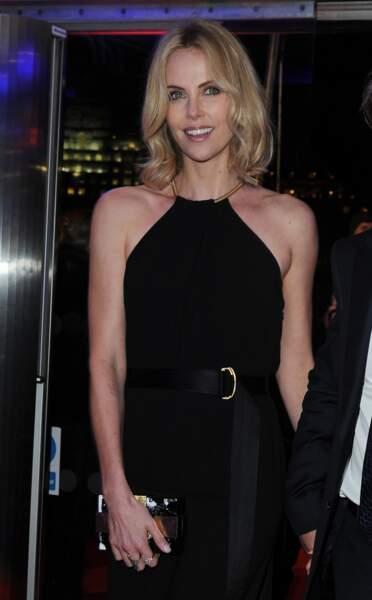 février 2015 : Charlize Theron a de nouveau les cheveux mi-long, elle porte une robe noir magnifique et ses cheveux ondulent naturellement.