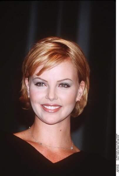 1998 : Charlize Theron porte une coupe au carré courte. Pour cette fin d'année elle a les cheveux roux.