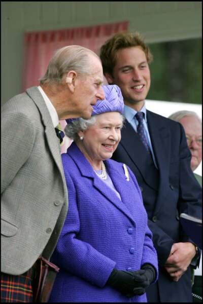 """2005 : La Reine Elizabeth II, le prince Philip et le prince William s'amusent lors d'un """"Braemar Royal Highland Gathering""""."""