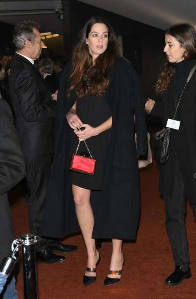Anouchka Delon porte une robe noire au-dessus du genou et de hauts talons.