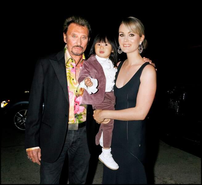 Johnny Hallyday et sa famille se rendaient à l'anniversaire d'un de ses amis où il allait donner un concert. La petite jade qui porte déjà son éternelle frange,  est en costume violacé. La photo fut prise en 2006 à l'occasion d'un concert de Chantal Goya.