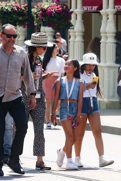 Jade Hallyday est avec Joy, Jean Reno et sa femme, zofia Borucka lors d'un week-end à Disneyland en juin 2019. Short en jean et bob fixé sur la tête, jade porte un look simple et efficace pour l'été.