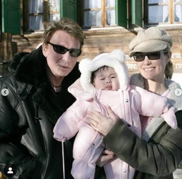Jade Hallyday lorsqu'elle était bébé, accompagnée de ses parents, Johnny et Laeticia Hallyday.  Jade n'a pas encore 1 an sur la photo. Jade Hallyday est née le 3 août 2004 au Vietnam et a été adoptée en novembre 2004 par le couple Hallyday.