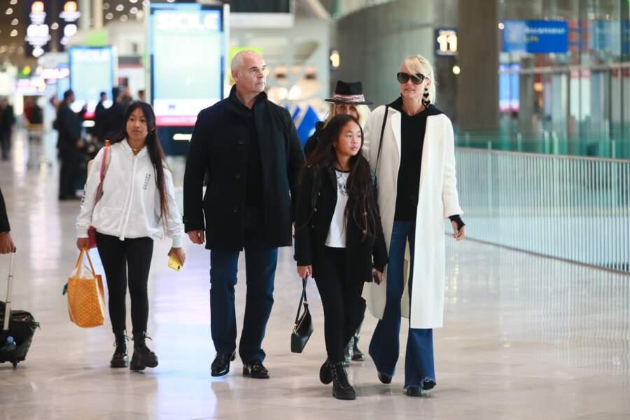 Jade Hallyday, accro aux marques de luxe, comme son sac Goyard. Ici avec sa famille à l'aéroport Roissy CDG le 19 novembre 2019.