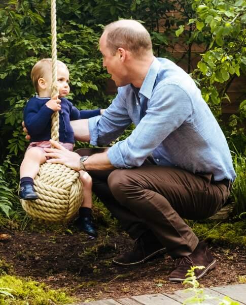Le prince Louis s'essayant à la balançoire - élément de décor voulu par Kate Middleton - sous le regard de son père William.