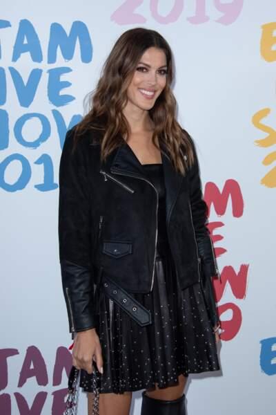 Iris Mittenaere très sexy en petite robe noire et veste perfecto en daim zippée.