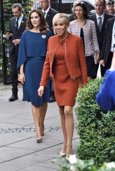 """Brigitte Macron très chic dans un total look orange dont la veste perfecto sans col apporte une touche de modernité à sa robe courte """"classy""""."""