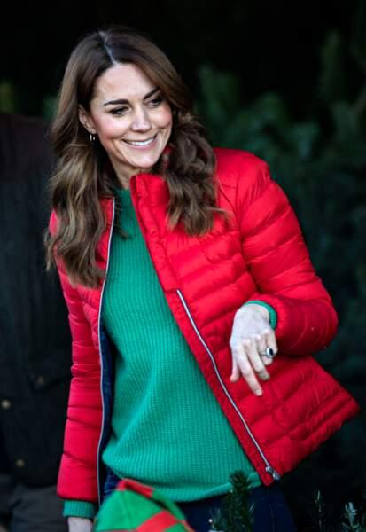 Kate Middleton a pris de l'assurance, elle s'amuse à mixer les couleurs comme ce pull vert sous une doudoune rouge, esprit de noel 2019 moderne.