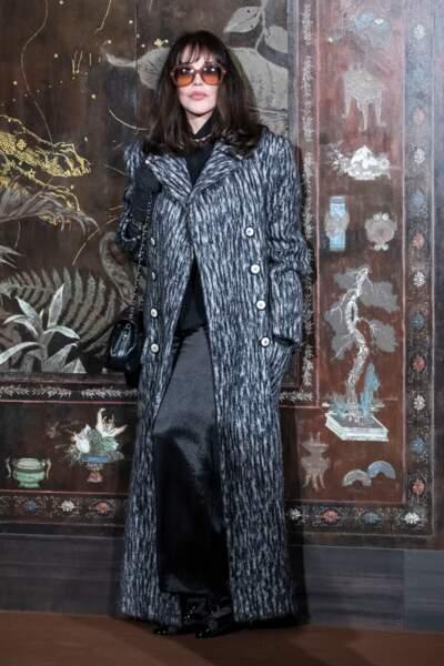 Isabelle Adjani, cachée sous ses solaires XXL un brin rétro, a opté pour l'élégance d'un long manteau gris chiné et d'un pantalon large noir satiné.