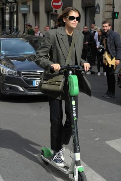 A la Fashion Week de Paris, Kaia Gerber adopte la trottinette dans les rues de la capitale, jamais sans son The Story Bag de Alexander McQueen.