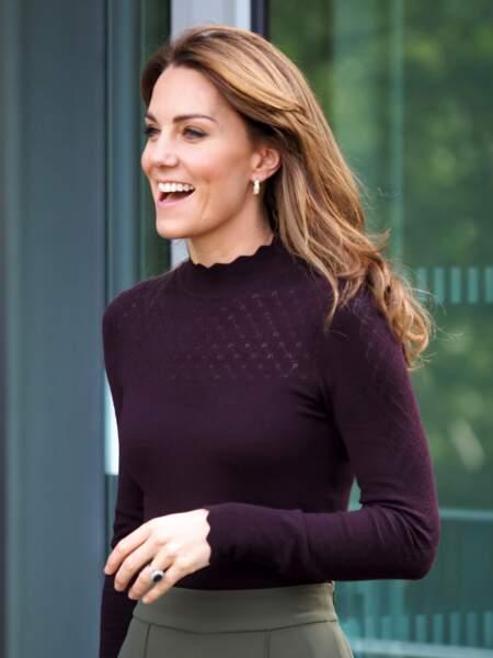 Tout est parfait dans ce look de Kate Middleton : le top violet, la jupe culotte verte, le sac Chanel vintage et les cheveux lissés et couleur miel, le 9 octobre 2019.