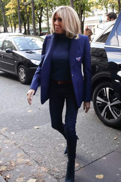 Brigitte Macron décontractée-chic en jean slim assorti à une petite veste blazer bleu nuit.