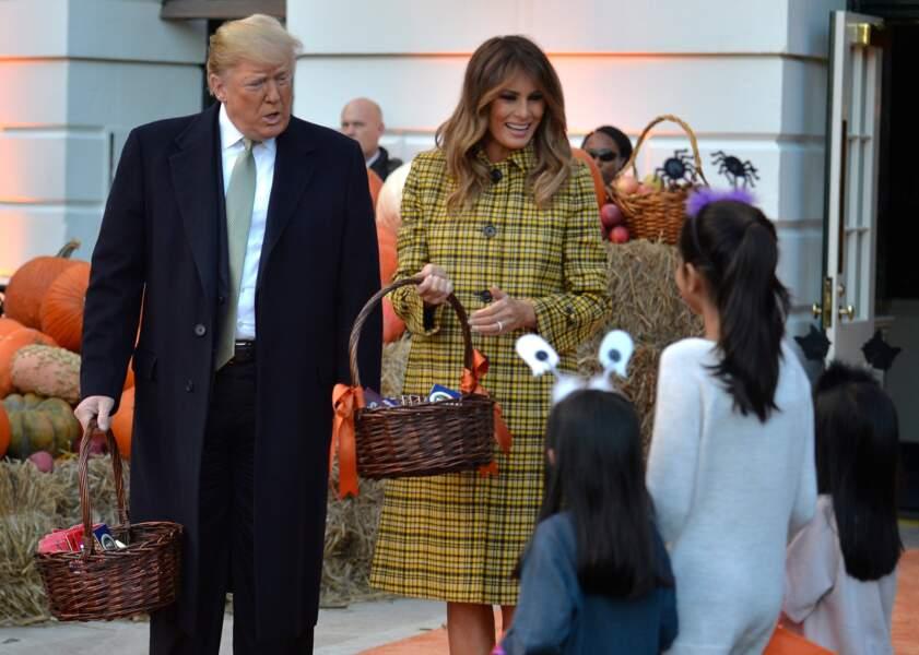 Melania Trump ose un manteau écossais jaune signé Bottega Veneta pour la distribution de sucreries à la Maison Blanche à l'occasion d'Halloween, le 28 octobre 2018.