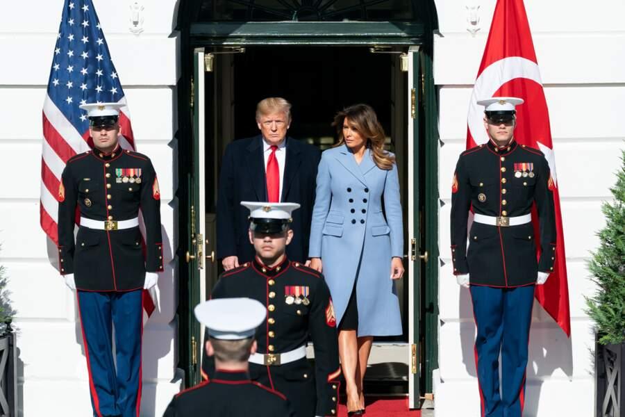 Melania Trump ose la tendance pastel dans un manteau droit bleu ciel au double boutonnage de la marque Altuzarra au prix de 1.845 euros pour recevoir le couple présidentiel turc à la Maison Blanche, le 13 novembre 2019.