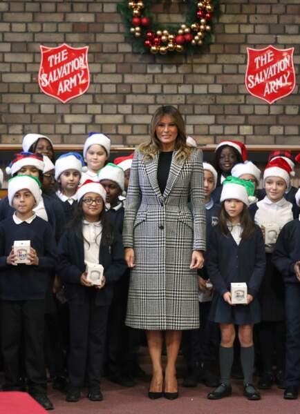 Melania Trump ose la tendance pied-de-poule sur un manteau long de de la marque Alexander McQueen estimé à 2.890 euros pour une distribution de cadeaux au Clapton Center de l'Armée du Salut, dans le nord de Londres, le 4 décembre 2019.