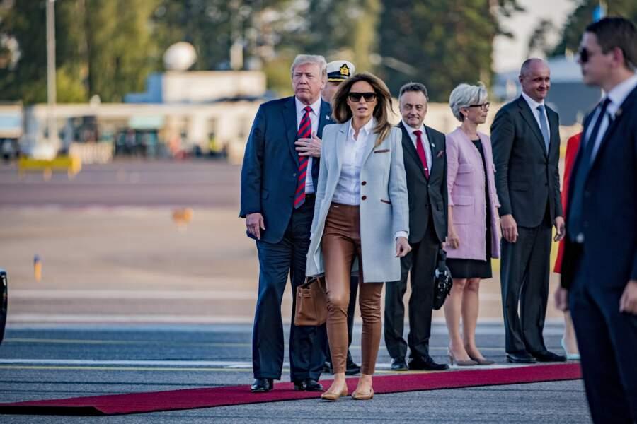Melania Trump chic en manteau gris et camel de la marque Isoude pour son arrivée à l'aéroport d'Helsinki, le 15 juillet 2018.