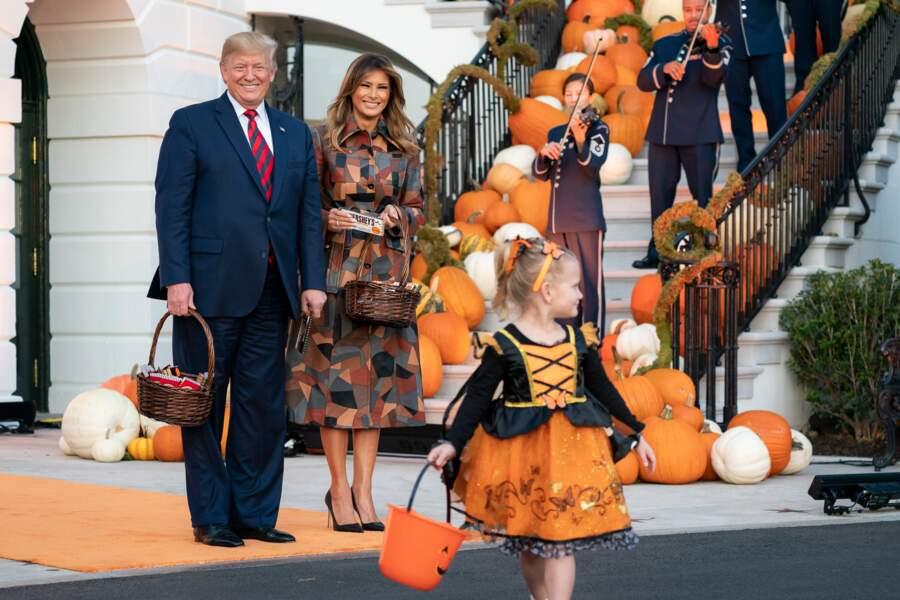 Melania Trump audacieuse dans un long trench-coat patchwork aux nuances automnales de la dernière collection Michael Kors pour célébrer Halloween à la Maison Blanche, le 31 octobre 2019.