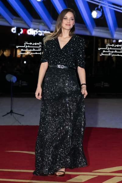 Marion Cotillard très chic dans un total look noir griffé Chanel en blouse vaporeuse à paillettes.