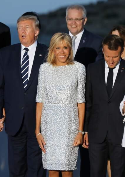 Brigitte Macron élégante dans une robe courte blanche sertie de strass argentés.
