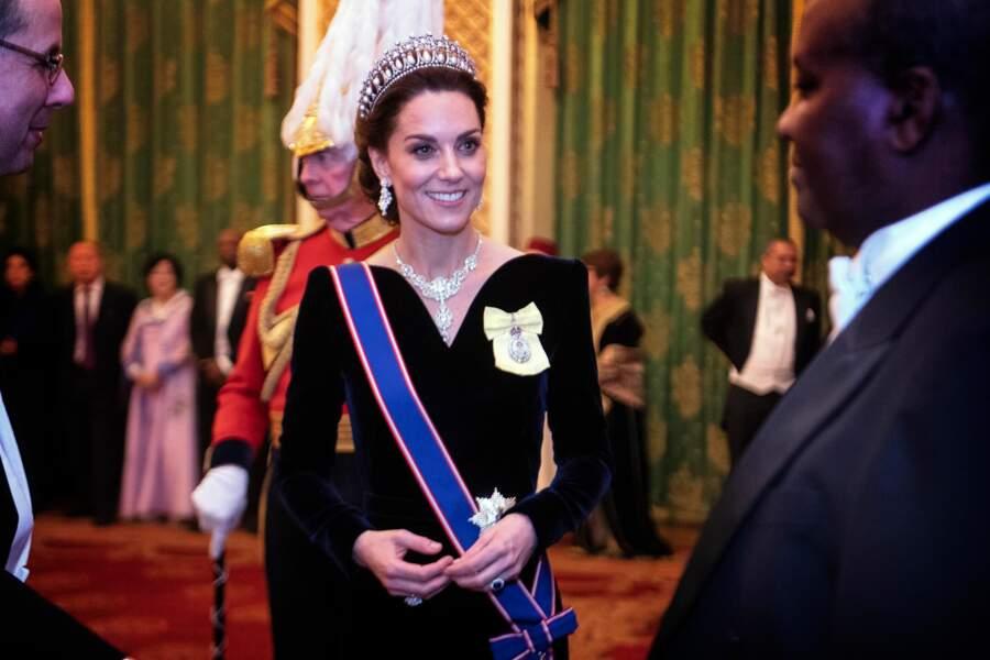 """Malgré la tiare et le collier très """"royals"""", Kate Middleton twiste avec une robe en velours au décolleté hollywoodien signé Alexander McQueen à Buckingham Palace, le 11 décembre 2019."""