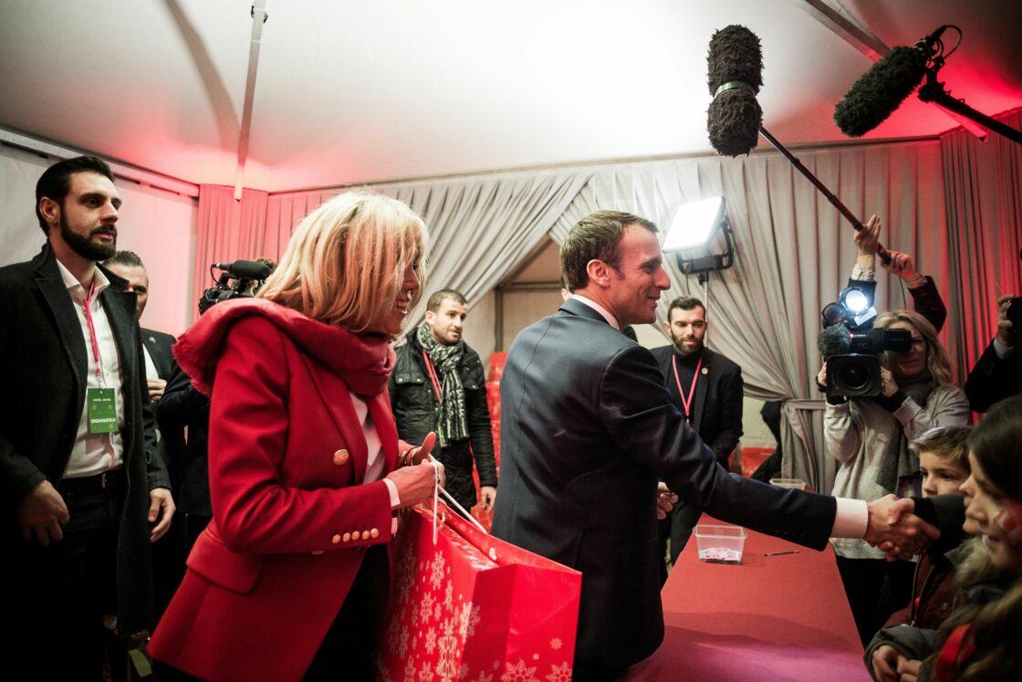 Brigitte et Emmanuel Macron distribuant les cadeaux à la Manufacture des Gobelins, le 19 décembre 2018.