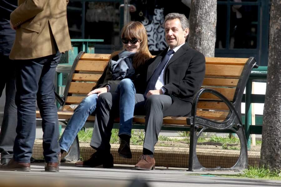 Mars 2014, Nicolas Sarkozy et sa femme Carla Bruni se délassent sur un banc, tout sourire. Moment de répit pour les amoureux.