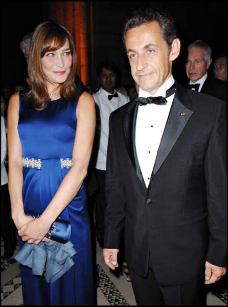 En Septembre 2008, Carla Bruni accompagne son mari lors d'un séjour à New York. La Première dame resplendit en robe bleue, au côté de son homme élégant en smoking noir.