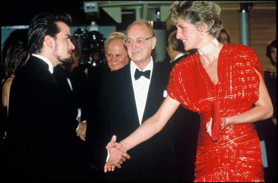 """La princesse Diana avec l'acteur Charlie Sheen lors de la première du film """"Hot Shots"""" à Londres en 1991. Elle porte en collier ras-de-cou en perles, diamants et rubis."""