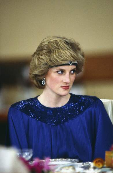 La princesse Diana, dans une robe bleu nuit dessiné par le couturier Yuki Torimaru, accessoirisée d'un bijou de tête en saphir, lors d'un voyage au Japon en 1986.