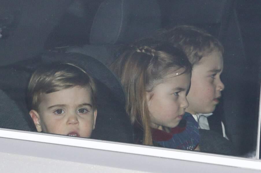 """Le prince Louis, ses aînés Charlotte et Louis quittant le traditionnel déjeuner de Noël organisé par la reine pour ses collaborateurs à Buckingham, le 18 décembre 2019 : un craquant cliché qui leur a valu le surnom """"Les Trois Mousquetaires"""" dans la presse anglaise."""