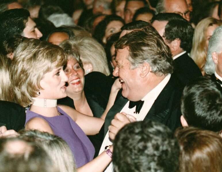 La princesse Diana, dansant avec l'homme d'affaire Michael Wilkie lors d'une soirée caritative à Chicago en 1996. Elle porte un collier tour de cou composé de onze rangées de perles.