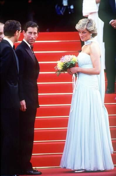 Charles et Diana sur les marches du Festival de Cannes 1987. La princesse est vêtue d'une robe Catherine Walker, accessoirisée de boucles d'oreilles en aigue-marine et diamants.