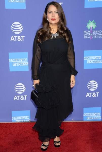 Salma Hayek sobre et chic en robe longue noire et les cheveux longs et ondulés.