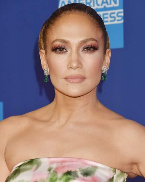 Jennifer Lopez a opté pour un joli bun et un joli fard rosé et orangé sur les yeux.