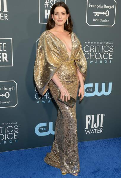 Anne Hathaway, qui a accouché de son deuxième enfant en décembre, rayonne dans cette robe très décolletée signée Atelier Versace.