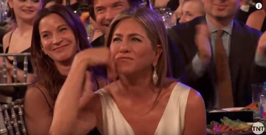 Jennifer Aniston écoute attentivement le discours de Brad Pitt.