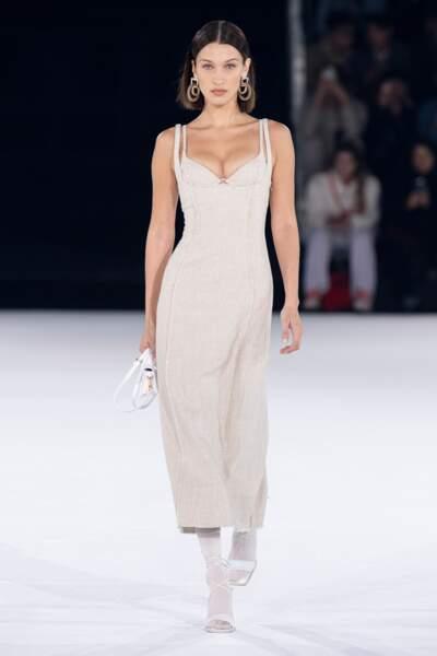 Une robe beige asseccoirisée de grandes bloucles d'oreilles et d'un des nouveaux sacs de la collection Jacquemus habillaient Bella Hadid.