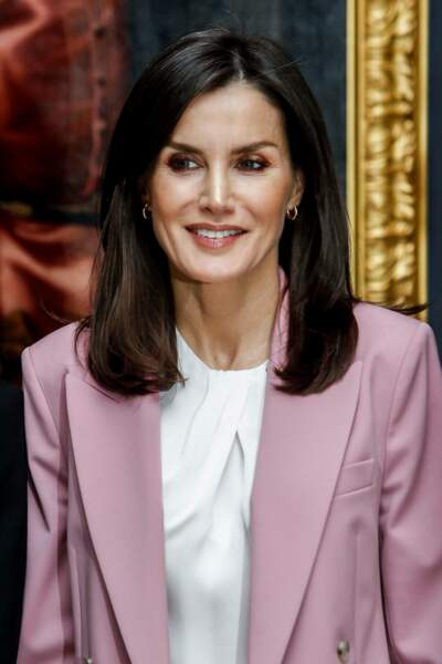17 décembre 2019 : La reine Letizia d'Espagne a foncé ses cheveux avec une coloration auburn. Son maquillage est très frais et le tailleur rose poudré lui va parfaitement au teint.