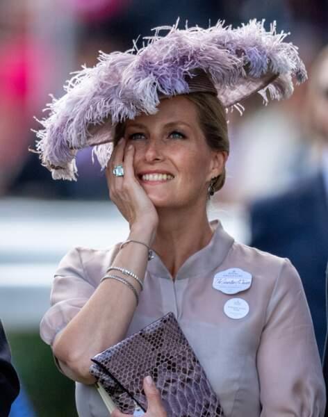 """Juin 2018 : Sophie de Wessex porte une sublime tenue lors du Royal Ascot 2018 dans le Berkshire. Très moderne, elle porte une blouse transparente associée à un petit sac style peau de serpent et un chapeau à plume couleur lilas. Un look """" bestial """" très stylé."""